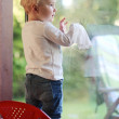 Baby girl cleaning window door with wet serviette — Stock Photo #42673565