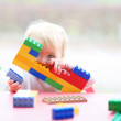 Girl playing peek-a-boo hiding behind plastic blocks — Stock Photo #42673625