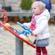 Girl having fun at the playground on winter — Stock Photo