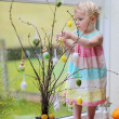 Adorable little blonde toddler girl decorating with Easter eggs cherry tree branches standing in the kitchen next a window with garden view — Stock Photo #42673851