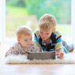 Boy with sister playing on tablet pc — Stock Photo #42673917