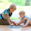 Girl playing puzzles with her teenager brother — Stock Photo #42674009