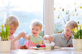 Group of cute children from one family, two twin brothers and their little toddler sister, decorating and painting Easter eggs sitting together in the kitchen on a sunny day. Selective focus on girl. — Stock Photo