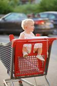 Baby girl sitting in red shopping cart — ストック写真