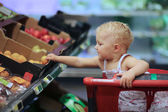 Baby girl picking up apricot from a box on shelf — Stock Photo