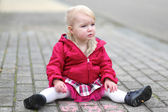 Girl drawing on asphalt with pink chalk — Stock Photo