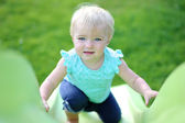 Baby girl playing on a green plastic slide in a park — Stock Photo