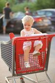 Baby girl sitting in red shopping cart — Stockfoto