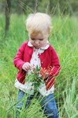 Baby girl playing in the autumn forest holding small rowan branch — Stock Photo
