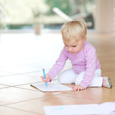 Baby girl drawing with colorful pencils — Stock Photo