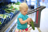 Girl looking at zucchini picked up from a shelf — Stock Photo