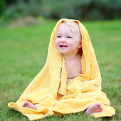 Baby in warm yellow towel sitting on the grass — Stock Photo