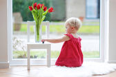Girl playing next to a big window with tulip flowers — Photo