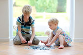 Girl playing puzzles with her brother — Stock Photo