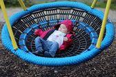 Baby flicka avkopplande på en gunga som netto på lekplats — Stockfoto