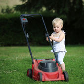 Baby girl is playing outside with lawn machine — Stock Photo