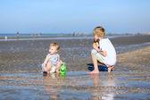 Pojke med hans syster som spelar på stranden — Stockfoto