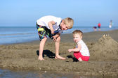 Boy and sister playing together at the beach — Stock Photo
