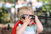 Baby girl playing peek a boo behind big sunglasses — Stock Photo