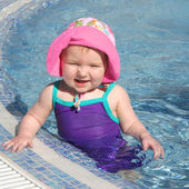 Baby girl having fun in little swimming pool — Stock Photo
