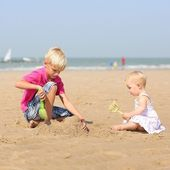 Boy and his little baby sister playing together at the beach — Stock Photo