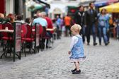 Baby girl standing on a busy crowded street — Stock Photo