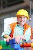 Boy building a house with big plastic construction bricks — Stock Photo