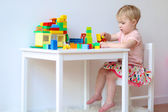 Girl building house from plastic blocks — Stock Photo