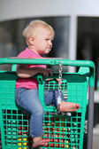 Baby girl sitting in a shopping trolley at a hypermarket — Stock Photo