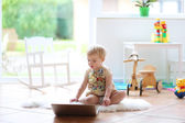 Girl playing with notebook indoors — Stock Photo