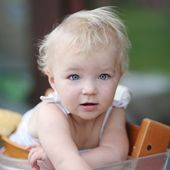 Baby girl  sitting on terrace in chair — Stock Photo