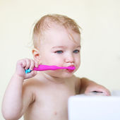Girl brushing her teeth in bathroom — Stock Photo
