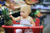 Baby girl sitting in red shopping cart — Stock Photo