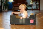 Baby girl plays with cardboard box sitting inside of it — Stock Photo