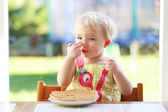 Girl eating delicious pancakes — Stock Photo