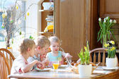 Group of three kids, twin brothers with their little toddler sister, eating eggs during family breakfast on Easter day sitting together in sunny kitchen. Selective focus on little girl. — Stock Photo
