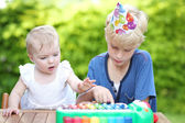 Boy playing with his sister at her first birthday party — Stock Photo