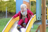 Girl having fun sliding on playground — Stockfoto