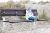 Girl on the bench next to sandy dunes — Stock Photo