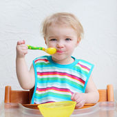 Girl eating porridge with spoon — Stock Photo
