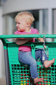 Baby sitting in a shopping trolley at a hypermarket — Stock Photo