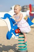 Baby girl rocking on a spring blue dolphin — Stock Photo