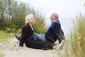 Senior couple sitting in the dunes — Stock Photo