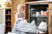 Flicka med plattor av skålen tvättmaskin — Stockfoto