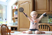 Girl playing with ladle and skimmer — Stock Photo