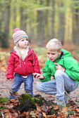 Brother and sister playing in the forest — Stock Photo
