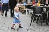 Baby girl standing next to chair of street cafe — Stock Photo