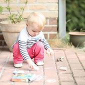Baby girl drawing with chalk — Stock Photo