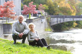 Smiling seniors at the shore of the river — Stock Photo