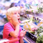 Boy looking at a price in fruits and vegetables — Stock Photo